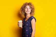 Affable Young Woman With Curly Hair Holds A Paper Cup On A Yellow Background.