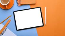 Empty Screen Of Digital Tablet On Two Tone Background With Office Supplies.