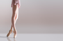 Ballerina's Feet In Pointe Shoes Standing Isolated On White Background