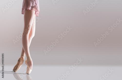 Ballerina's feet in pointe shoes standing isolated on white background Fototapeta