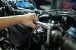 Mechanic using a wrench and socket on cylinder head of a motorcycle .maintenance,repair motorcycle concept in garage .selective focus