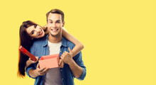 Love, Relationship, Dating, Flirting, Lovers, Romantic Concept - Happy Couple Opening Gift Box, Looking At Camera. Studio Portrait Of Young Man And Woman, Isolated Over Yellow Background.