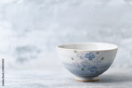 Traditional ceramic bowl on bright background. Copy space. Wallpaper Mural