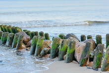Old Wooden Piles Of Breakwater In Sand By Sea. Beautiful Seascape. Selective Focus