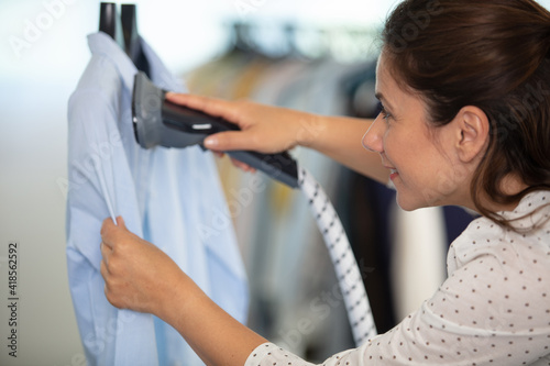 Obraz woman steaming shirt at dry-cleaners - fototapety do salonu