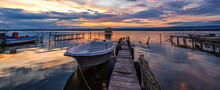Amazing Mood Sunset At A Lake Coast With A Boat At A Wooden Pier.