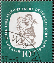 """GERMANY, DDR - CIRCA 1958 : A Postage Stamp From Germany, GDR Showing Two Playing Children (""""Zillegören""""). 100th Birthday Of Heinrich Zille"""