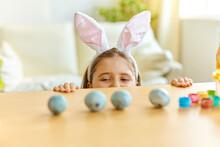 Little Girl Wearing Bunny Ears Playing Egg Hunt On Easter.