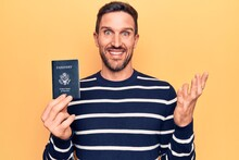 Young Handsome Tourist Man Holding United States Passport Over Isolated Yellow Background Celebrating Achievement With Happy Smile And Winner Expression With Raised Hand