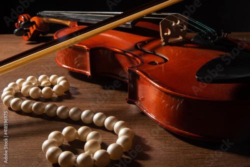 Obraz na plátně Violin and pearl necklace, arrangement with violin and pearl necklace on wooden surface, low key portrait, selective focus