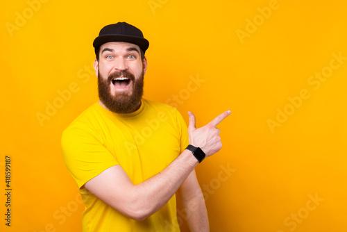 Cheerful happy bearded man in yellow tshirt pointing away and screaming Fototapeta
