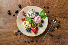 Three Balls Of Colorful Ice Cream On A Large Plate
