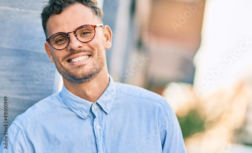 Obraz Young hispanic businessman smiling happy standing at the city. - fototapety do salonu