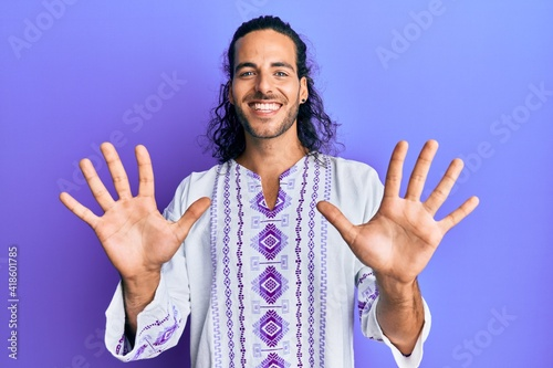 фотография Young handsome man with long hair wearing bohemian and hippie shirt showing and pointing up with fingers number ten while smiling confident and happy