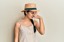 Young Hispanic Woman Wearing Summer Hat Surprised With Hand On Head For Mistake, Remember Error. Forgot, Bad Memory Concept.