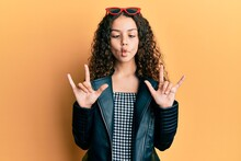 Teenager Hispanic Girl Doing Rock Gesture Making Fish Face With Mouth And Squinting Eyes, Crazy And Comical.