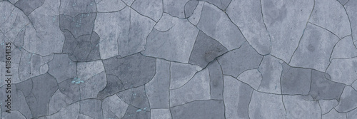 Obraz Peeling paint on the wall. Panorama of a concrete wall with old cracked flaking paint. Weathered rough painted surface with patterns of cracks and peeling. Panoramic texture for background and design. - fototapety do salonu