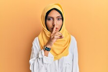 Young Brunette Arab Woman Wearing Traditional Islamic Hijab Scarf Asking To Be Quiet With Finger On Lips. Silence And Secret Concept.