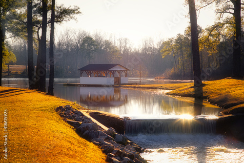Canvas A dreamy landscape of a lake boathouse during sunset with sun glare