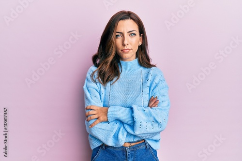 Young brunette woman wearing casual winter sweater over pink background skeptic and nervous, disapproving expression on face with crossed arms Fotobehang