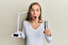 Young Blonde Woman Holding Solar Windmill For Renewable Electricity And Led Light Bulb Afraid And Shocked With Surprise And Amazed Expression, Fear And Excited Face.