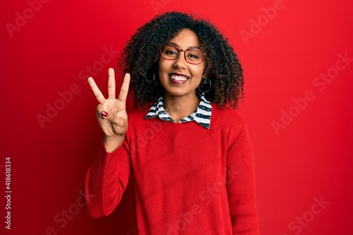Wallpaper Mural Beautiful african american woman with afro hair wearing sweater and glasses showing and pointing up with fingers number three while smiling confident and happy
