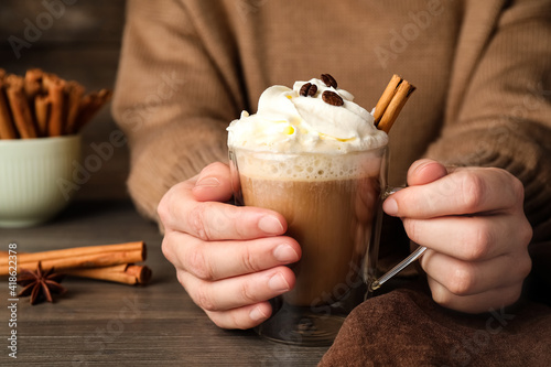 Woman holding cup of delicious coffee with whipped cream and cinnamon at wooden table, closeup © New Africa