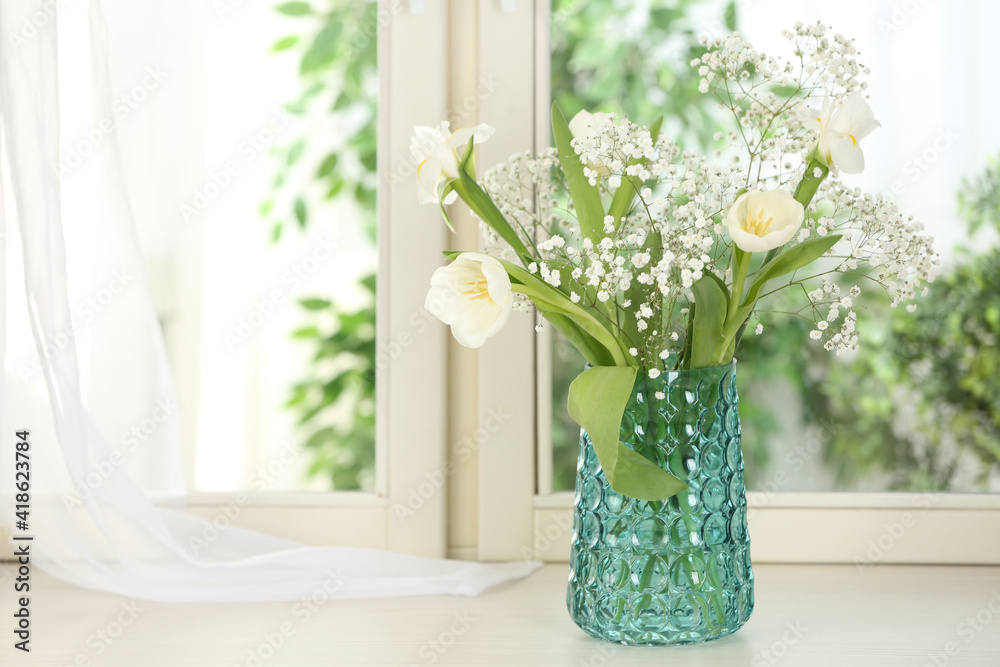 Fototapeta Beautiful fresh flowers on window sill indoors. Space for text