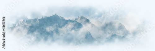 Obraz Mountain peaks in the clouds, vignette. Panoramic view. - fototapety do salonu