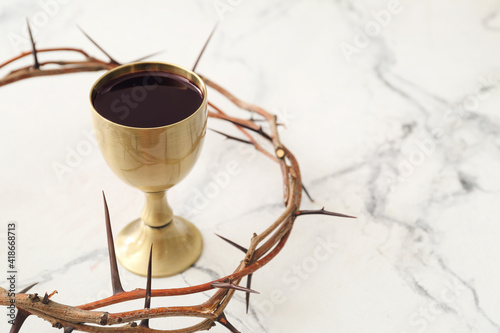 Fotografia, Obraz Chalice of wine and crown of thorns on white background