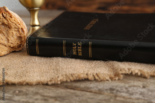 Fototapeta Holy Bible with bread on wooden table