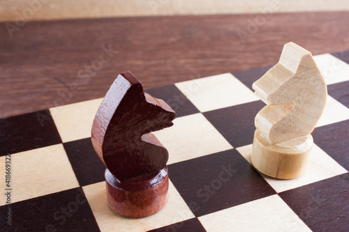 Slika na platnu educational chess, white and black knight pieces on a chessboard, selective focu
