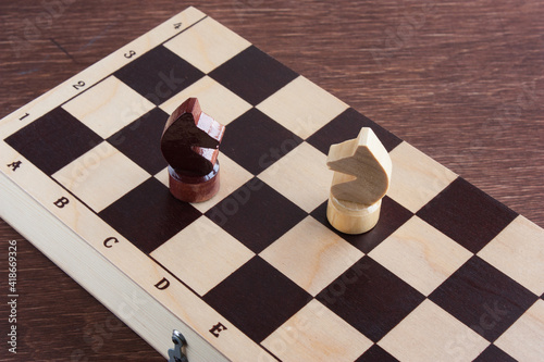 Valokuva educational chess, white and black knight pieces on a chessboard, selective focu