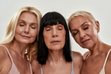 Mature Beauty. Three Middle Aged Women Keeping Eyes Closed While Staying Next To Each Other