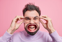 Emotional Burnout. Headshot Of Bearded Adult Man Feels Huge Pressure Shouts Angrily Clenches Teeth Keeps Hands On Transparent Glasses Squints Face Expresses Anger Isolated Over Pink Background