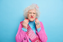 Portrait Of Stylish Elderly Woman With Grey Curly Hair Pouts Red Painted Lips Makes Unhappy Griace Wears Fashionable Clothes And Small Crown On Head Celebrates Birhday Want To Be Always Young