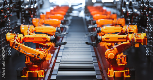 Robotic arms along assembly line in modern factory.