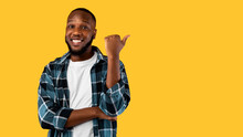Cheerful Black Guy Pointing Thumb Aside Standing Over Yellow Background