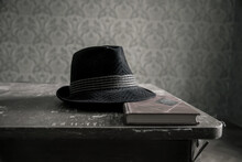 An Antique Hat And A Book Lie On A Table In An Abandoned House. Old Room.