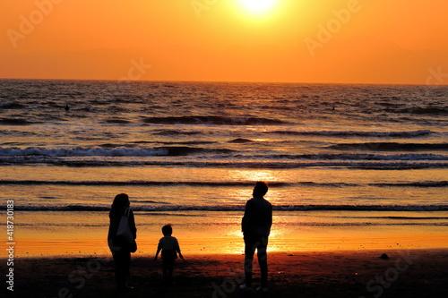 湘南海岸の夕日を眺める親子連れ Fototapete