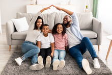 Black Parents Making Symbolic Roof Of Hands Above Their Children