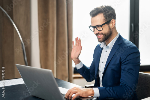 Tablou Canvas Video call concept, young good-looking man wearing suit and glasses is using a l