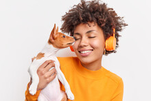 Display Of Affection And Love. Positive Sincere Dark Skinned Woman Gets Kiss From Favorite Pet Has Fun Loves Her Dog Wears Stereo Headphones Listens Music Dressed In Orange Jumper Poses Indoor
