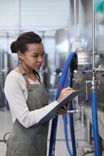 Vertical Portrait Of Young African-American Woman Holding Clipboard While Inspecting Production Quality At Industrial Food Factory, Copy Space