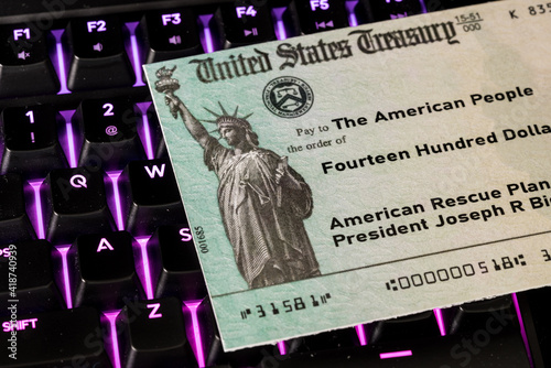 US Treasury concept check to illustrate coronavirus stimulus payment on keyboard used for working from home © steheap