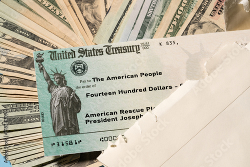 Stack of 20 dollar bills with US Treasury illustrative check to illustrate American Rescue Plan Act of 2021 payment on cash background © steheap