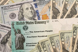 Stack of 20 dollar bills with US Treasury illustrative check to illustrate American Rescue Plan Act of 2021 payment on cash background