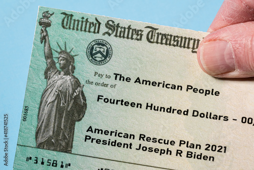 Hand holding a US Treasury illustrative check to illustrate American Rescue Plan Act of 2021 payment on blue background © steheap