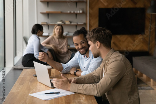 Photographie Happy diverse colleagues working on financial project together, sitting at table