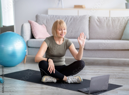 Fotografie, Tablou Happy mature woman in sportswear sitting on yoga mat in front of laptop, greetin